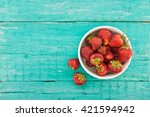 Fresh strawberries in a ceramic bowl on turquoise rustic wooden background. Top view. - stock photo