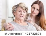 Small photo of Close-up of a granddaughter holding her grandmother affectionately