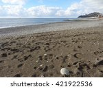 Empty beach, sand and pebble, clouds over the sea                               - stock photo