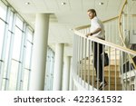 Small photo of Young businessman walking up the stairs in the office building