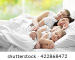 Family Sleeping In Bed On...
