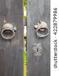 Small photo of Two old iron ring handles and lock on an old weathered wooden door standing ajar showing a glimpse of a garden