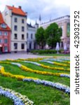 Small photo of Liv area with flowers and green lawn in the old city of Riga in spring. Blurred