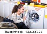 smiling brunette girl selecting ... | Shutterstock . vector #423166726