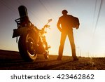 Biker With Motorbike Stands On...