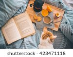 Stock photo breakfast served in bed boiled egg fresh orange cookies and coffee while reading a book and 423471118