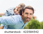 happy father giving piggyback... | Shutterstock . vector #423584542