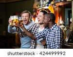 happy men with beer in pub | Shutterstock . vector #424499992