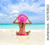 Small photo of Perfect paradise summer vacation happiness carefree happy woman relaxing sitting in sand enjoying tropical beach destination. Back view of bikini girl holding pink straw hat on Caribbean holiday.