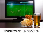 Small photo of Pint of beer on the table in front of television show off football.