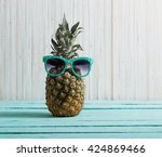 ripe pineapple on a wooden table | Shutterstock . vector #424869466