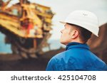 Small photo of Coal mining in an open pit - Worker is looking on the huge excavator - industry in Czech Republic