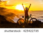 Success, achievement, accomplishment and winning concept with cyclist mountain biking. Winning happy MTB woman cycling reaching goal raising arms at sunset cheering and celebrating at summit top. - stock photo