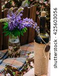 Small photo of Ajar decorated bottle of wine an a branch of purple field luppin flowers in a crafted vase on a picnic plaid.