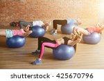 cheerful sporty girls do sit ups   Shutterstock . vector #425670796
