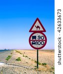 road sign with camel in the middle of the desert - stock photo