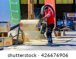 Small photo of Emmaboda, Sweden - May 13, 2016: Forest and tractor (Skog och traktor) fair. Kaha Nui Wood lumberjack sports show. Person sawing large slices of a tree trunk or log with powerful chainsaw.