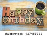 Small photo of Happy Birthday greeting card - word abstract in vintage letterpress wood type stained by color inks with a green stoneware cup of coffee