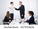 Small photo of Group Of Businesspeople Looking At Businessman Blaming His Colleague In Meeting