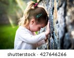 Small photo of emotion girl sitting near wall in the day time, beautiful background