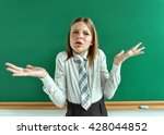 Small photo of What's amiss? Perturbed girl near blackboard with divorced his hands