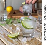 Small photo of square image. A young girl is preparing an alcoholic or non-alcoholic cocktail, hands, bartender, bar, restaurant, mint, lime, lemon, alcoholic, non-alcoholic