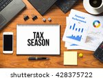 Small photo of Office desk table with notebook written TAX SEASON with laptop, smartphone, cup of coffee, pen, calculator, dice, clips, file and a paper of charts - Business concept top view.