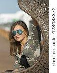 woman sitting on a wicker swing ... | Shutterstock . vector #428488372