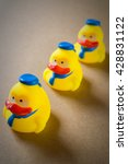 Small photo of Three little yellow rubber duckling with blue hat arranged align and diagonal (selective focus on one rubber duck as leader)