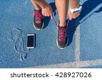 Small photo of Runner woman tying running shoes laces getting ready for race on run track with smartphone and earphones for music listening on mobile phone. Athlete preparing for cardio training. Feet on ground.