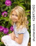 pretty curly blond girl sitting ... | Shutterstock . vector #428971402