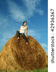 Portrait of young female sitting on hay bale - stock photo