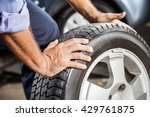 mechanic holding car tire at... | Shutterstock . vector #429761875