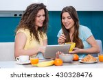Small photo of Two woman friends taking breakfast in the kitchen and having fun, talking and laughing. catching up on social media on tablet deice as sitting at the dining table at home.