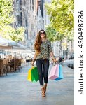 Small photo of Getting unique trends of Barcelona. Full length portrait of happy fashion-monger woman with shopping bags walking down the street