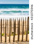 Small photo of Wooden fence on an Atlantic beach in France, The Gironde Department. Shot with a selective focus