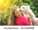 Stock photo puppy white dog licking it s owner attractive caucasian girl having fun with her dog 431268988