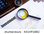 "Small photo of Magnifying glass on colourful pie chart with ""Investment"" text on paper, dice, spectacles, pen, laptop calculator on wooden table - business, banking, finance and investment concept"