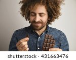 Small photo of Young happy bearded man with healthy skin and curly hair pleasured with taste of organic freshly baked chocolate bar,holds one small piece in one hand and bar in other