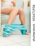 Small photo of Woman with constipation or diarrhoea sitting on toilet with her blue pajamas down around her legs