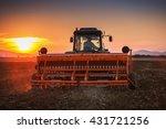 Farmer With Tractor Seeding...