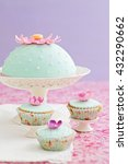 Small photo of Round cake and three cupcakes decorated with fondant and gum paste flowers