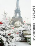 Rare snowy day in Paris. The Eiffel Tower and decorated Christmas tree - stock photo