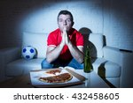 Small photo of crazy fanatic man football fan watching football game on television wearing red team jersey suffering nervous and stress praying god on sofa couch at home with soccer ball beer bottle and pizza