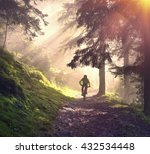 fog rider on a mountain bike overcome challenging tracks in the wild alpine forest at dawn on a background of the sun during the Ukrainian Carpathian marathon for off-road trails in the Carpathians - stock photo