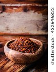 Small photo of Pul biber - crushed red chili pepper in vintage bowl on wooden background. Selective focus. Toned image. Turkish cuisine