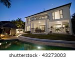 Luxurious mansion exterior at dusk overlooking pool - stock photo