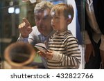 Small photo of Father And Son Look At Artifacts In Case On Trip To Museum