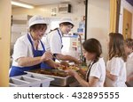 Stock photo two women serving food to a girl in a school cafeteria queue 432895555