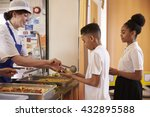 Stock photo dinner lady serving kids in a school cafeteria side view 432895588
